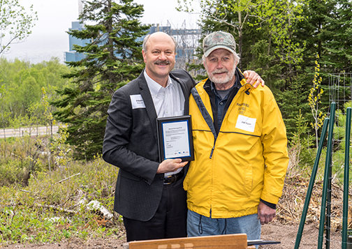 Al Hodnik holds a plaque given to Jack Rajala, chief executive of Rajala Companies, in appreciation of his work to restore the white pine to northern Minnesota.