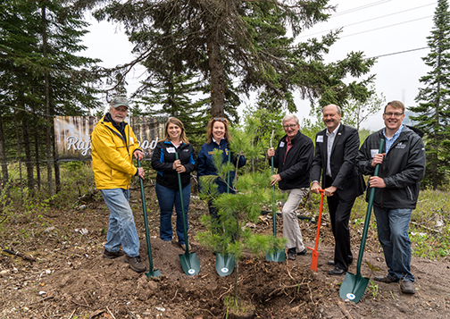 Jack Rajala, Deb Amberg, Lori Dowling-Hanson, Jack Hedstrom, Al Hodnik and Al Rudeck, Minnesota Power vice president of strategy and planning, prepare to ceremoniously plant a larger tree.
